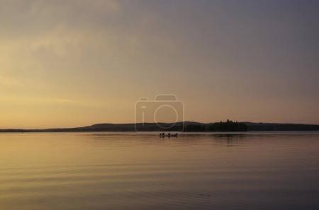 Photo pour Paysage paisible en soirée. Silhouette de personnes naviguant sur un bateau au-dessus de la rivière après le coucher du soleil. fond brumeux gris . - image libre de droit