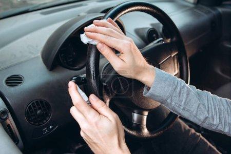 Photo pour Le gars utilise un désinfectant pendant qu'il conduit une voiture. Précautions pendant l'épidémie de coronavirus. Fusible de COVID-19. Un homme dans un masque médical dans une voiture . - image libre de droit
