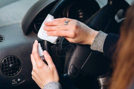 Photo pour Fille utilise un désinfectant tout en conduisant une voiture. Précautions pendant l'épidémie de coronavirus. Fusible de COVID-19. fille dans un masque médical dans une voiture. - image libre de droit