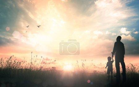 Photo pour Concept de journée internationale des migrants: Silhouettes père et fils tenant la main dans la main sur fond de coucher de soleil automne pré. - image libre de droit