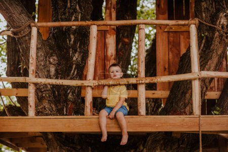 Photo for Little cute barefooted boy in summer yellow shirt on a tree house - Royalty Free Image
