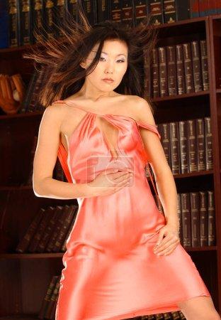 Photo pour Oriental asiatique brunette debout posant dans la bibliothèque de livres portant pêche satin brillant slip conservateur mais sexy séduisant et sensuel mince heure forme de verre naturel perky suggestive provocateur beauté vilaine collège fille pinup affiche - image libre de droit