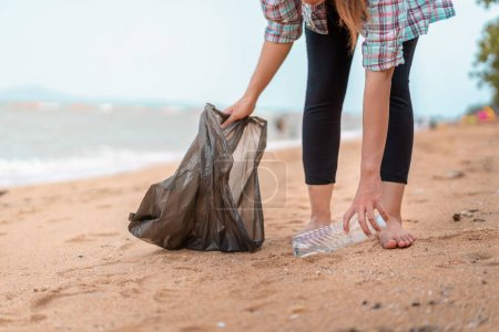 Photo for Asian woman picking  bottle into plastic bag black for cleaning the beach in morning time, Volunteer concept. - Royalty Free Image