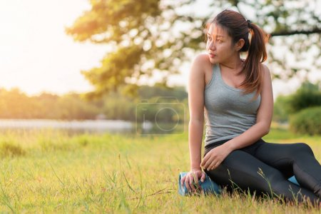 Photo for Young asian woman wearing exercise suit and sit on blue yoga mat or fitness mat after practicing yoga in park, Healthy concept, Mind-body improvements concept. - Royalty Free Image
