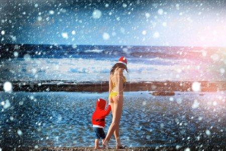 santa boy and woman at beach