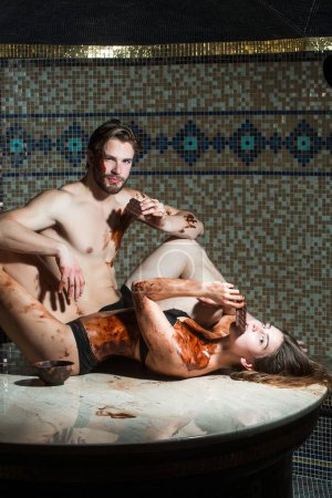 muscular man and sexy woman eat chocolate after salon massage