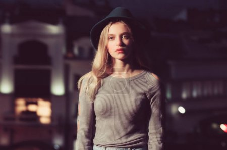 girl with hat in profile against night city background