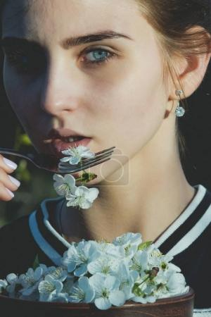 woman eating cherry blossom petals with metallic fork