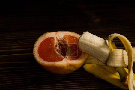 Photo pour Pamplemousse et banane avec pelure jaune sur fond en bois, le sexe et les rapports sexuels, l'amour fruits, vitamine et régimes amaigrissants, saine alimentation, pénis et vagin - image libre de droit