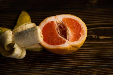 Photo pour Pénis et vagin, banane avec pelure jaune au pamplemousse rouge sur fond en bois, le sexe et les rapports sexuels, amour de fruit, vitamine et régimes amaigrissants, des aliments sains - image libre de droit