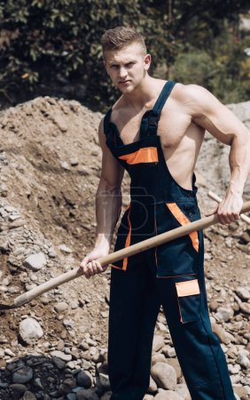 Muscular builder on sunny day works at construction site.