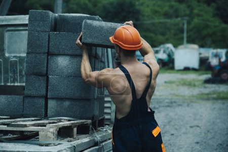 Muscular builder in hard hat wears overalls.