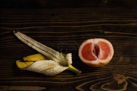 Photo pour Pamplemousse rouge et peau de banane jaune sur fond en bois, fruits amour et été, vitamine et suivre un régime, alimentation saine, pénis et vagin - image libre de droit