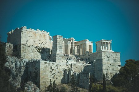 Ruins of ancient acropolis athens surrounded by park or forest. Old building with columns on high platform made out of bricks, sky background. Cultural and architectural heritage concept.