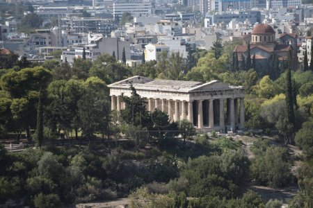 Ruins of ancient Greek temple surrounded by park or forest. Old building with columns with modern city, urban background. Confrontation of ages. Cultural and architectural heritage.
