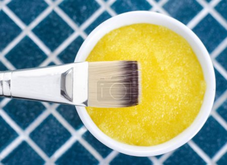 Yellow cosmetic mask (scrub) in a bowl, top view