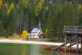 A beautiful autumn picture of the church near the lake on Fanes-