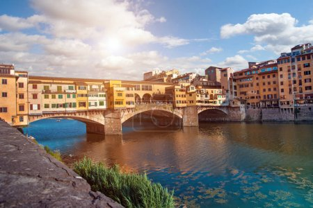 Photo for Beautiful city view with the famous medieval stone bridge Ponte Vecchio over the Arno river in Florence, Italy. Place of pilgrimage for tourists. - Royalty Free Image