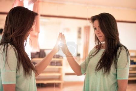 Photo pour Charmante jeune jolie fille aux cheveux luxueux touche son reflet dans un miroir dans la lueur de la lumière - image libre de droit