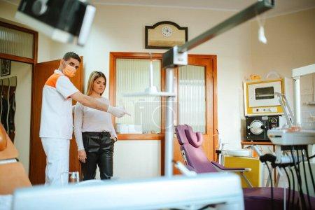 Photo pour Un jeune dentiste caucasien avec un masque montre une belle patiente caucasienne s'asseoir sur une chaise dans le bureau du dentiste - image libre de droit