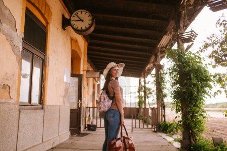 Photo pour Face arrière d'une jeune femme caucasienne dans une vieille gare avec un chapeau de paille et une valise à la main - image libre de droit