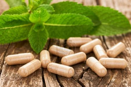 Photo for Natural medicine in capsules leaning on an old wooden table against the background of green leaves - Royalty Free Image