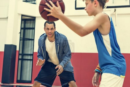 man and boy playing basketball