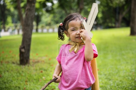 Girl with wooden sword in park
