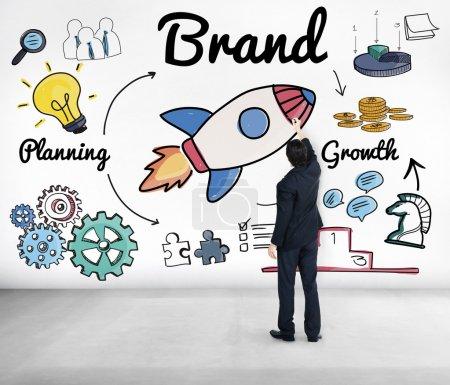 Businessman stands near wall Brand