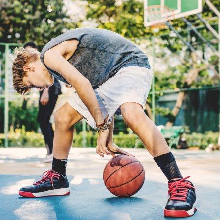 man and  boy playing basketball