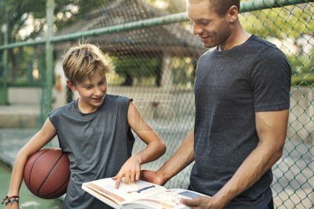 man and boy learning how to play basketball