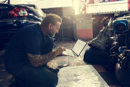 car mechanic using laptop in garage