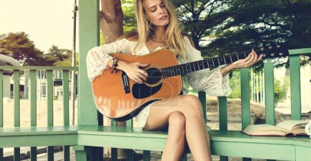 Blonde woman Playing acoustic Guitar
