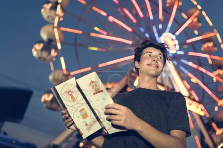 young man with map in amusement park