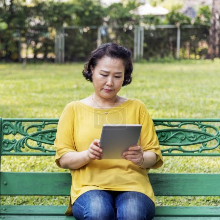 Adult asian woman using tablet
