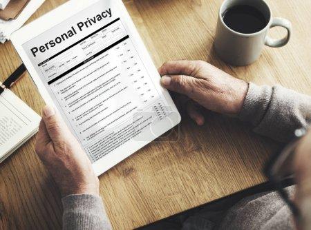 Photo pour L'homme à l'aide de tablette numérique à la table de travail en bois, texte à l'écran: la vie privée - image libre de droit