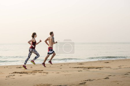 Woman and man running on the beach