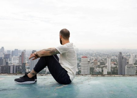 Man Sitting on Rooftop