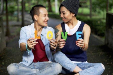 Lesbian Couple holding letters