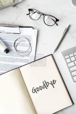 Photo pour Table de travail avec le livre ouvert, lunettes, clavier et stylet, texte dans le journal: au revoir - image libre de droit