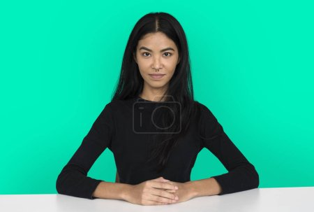 Asian woman sits by table