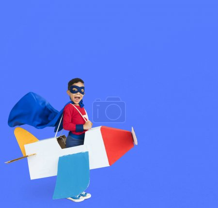 Boy playing with paper airplane