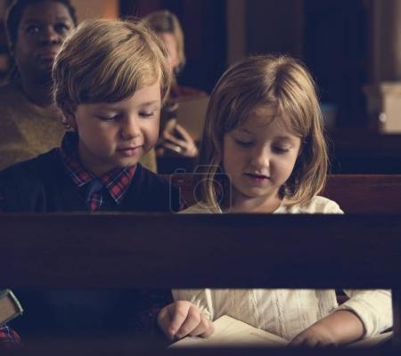 children reading book in church