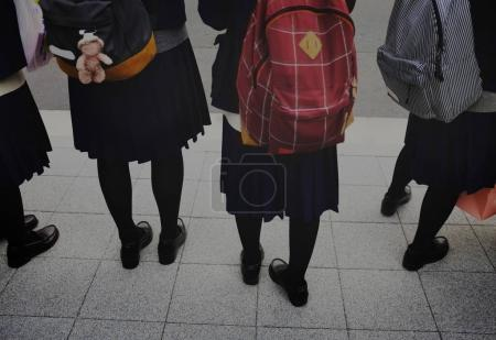 pupils in uniforms with backpacks