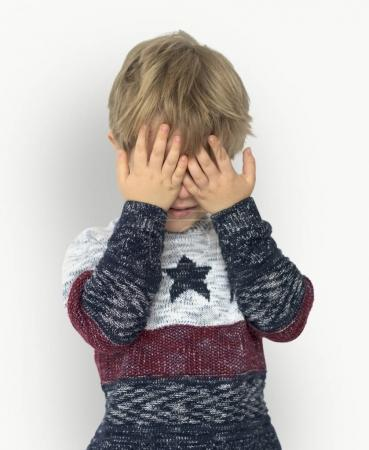boy closing eyes with hands
