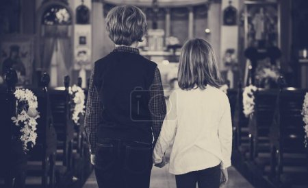 Children holding hands standing in church