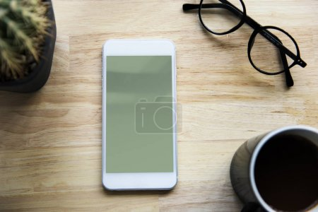 Smartphone on wooden table with eyeglasses