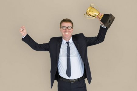 Business Man holding golden trophy