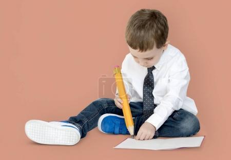boy writing with big pencil