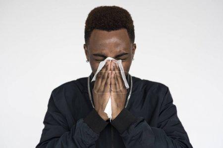 sick African man sneezing